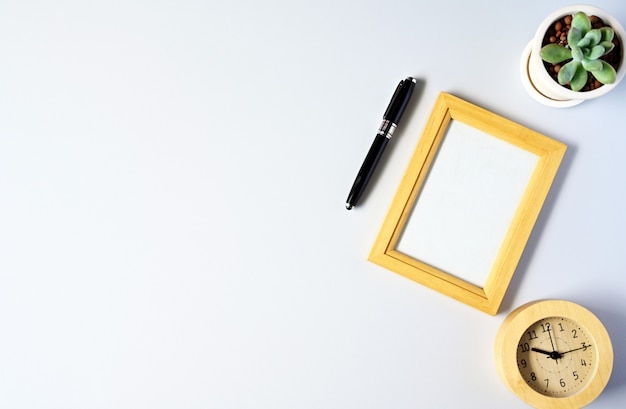 Working with picture frame and succulent copyspace on white table background Premium Photo