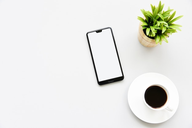Working with smartphone, hot coffee and plant copy space on desk background Premium Photo
