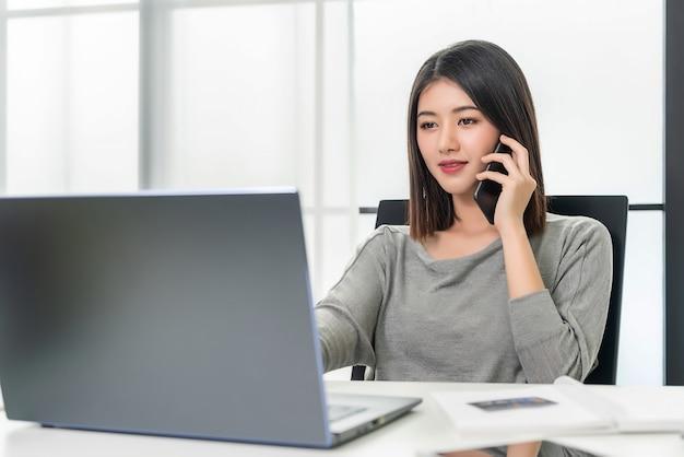 携帯電話で話している働く女性 Premium写真