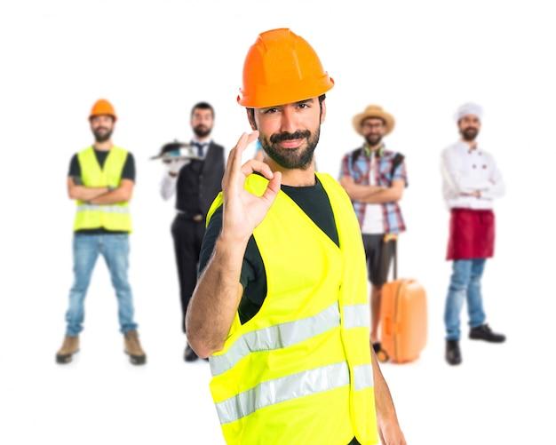 Workman making ok sign over white background Free Photo