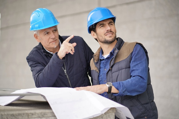 Workman pointing and showing something to employee on modern building sight Premium Photo