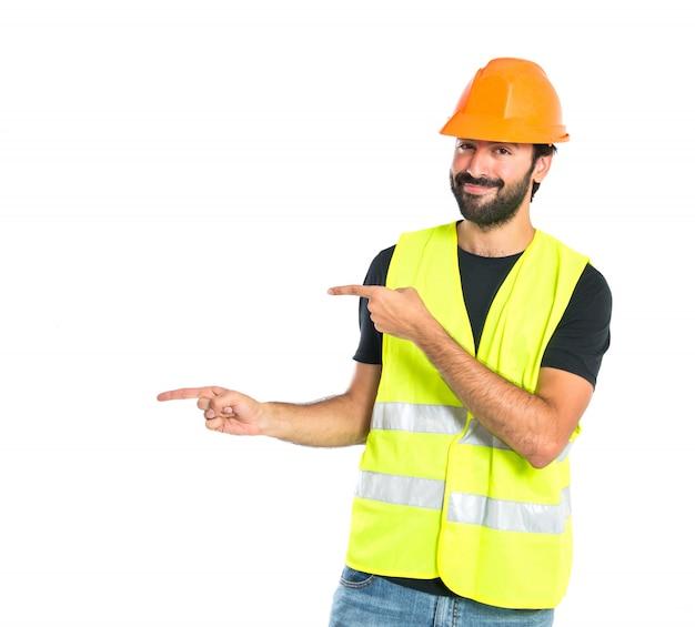 白い背景の上でlatertalを指している労働者 無料写真