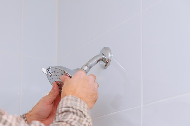 Workman repairing shower head in bathroom Premium Photo