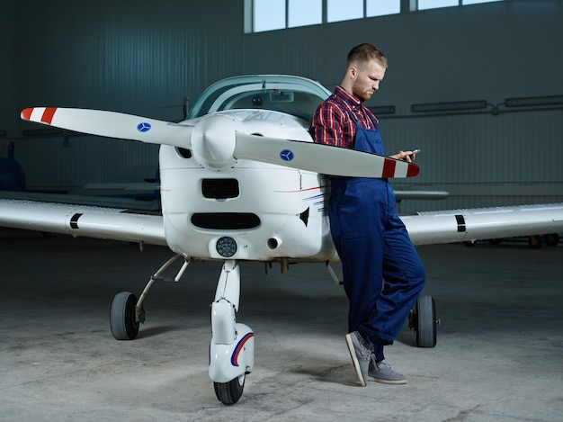Workman with smartphone and a plane Free Photo