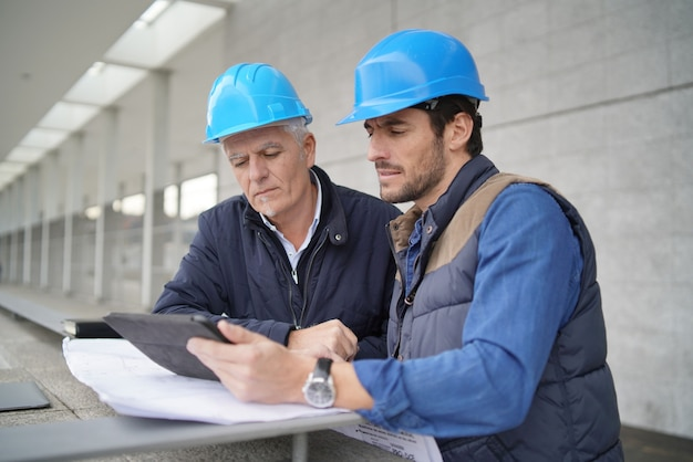 Workmen consulting over blueprint with tablet on modern building sight Premium Photo