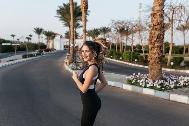 Тренировка на улице с пальмами привлекательной молодой женщины в спортивной улыбке. выражение позитивности, истинных эмоций, здорового образа жизни, тренировок, солнечного утра. Бесплатные Фотографии