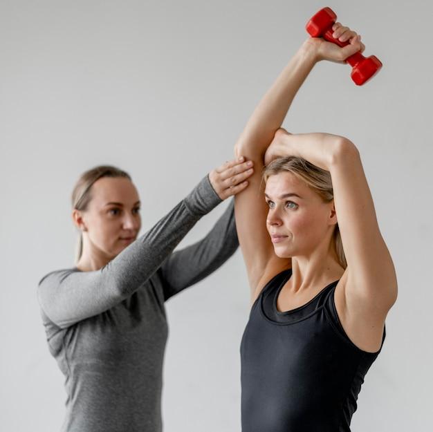 パーソナルトレーナーとダンベルミディアムショットでのトレーニング 無料写真