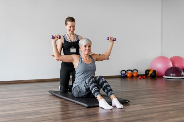 Тренировка с личным тренером упражнение для рук с гантелями Бесплатные Фотографии