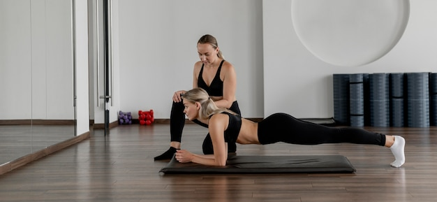 Workout with personal trainer doing planks long shot Free Photo