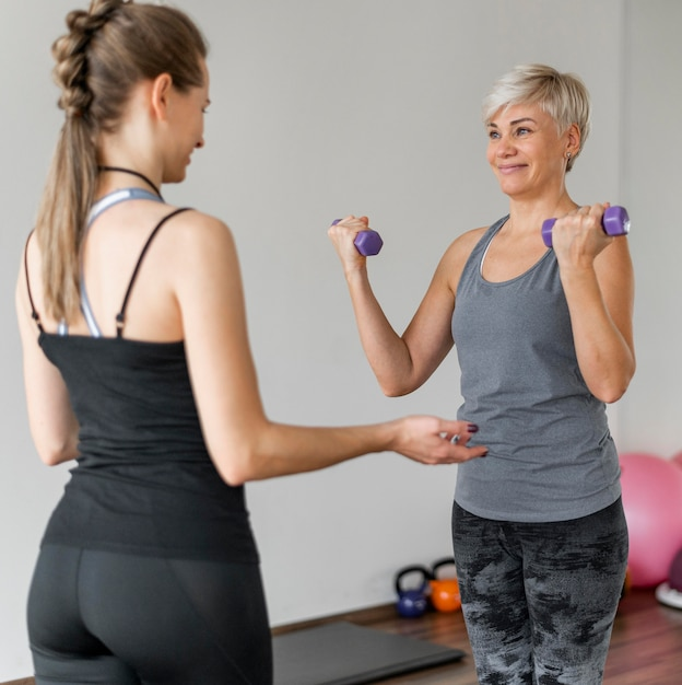 Тренировка с персональным тренером с использованием фиолетовых гантелей Бесплатные Фотографии