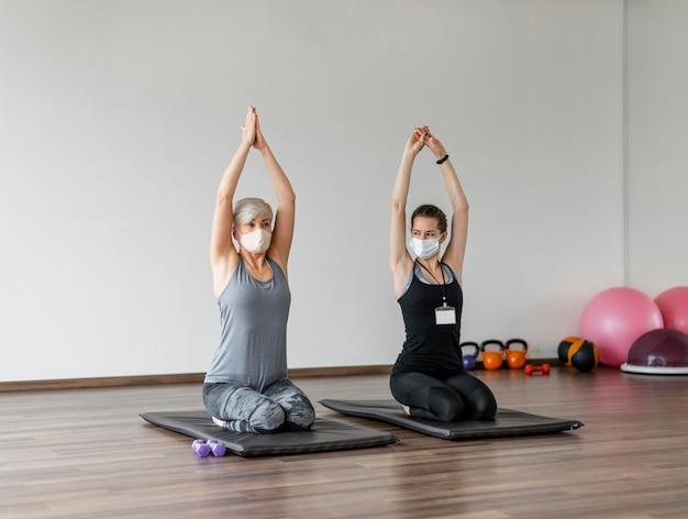 ファブリックマスクを着用したパーソナルトレーナーとのトレーニング 無料写真