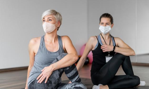 마스크를 착용 한 개인 트레이너와 함께 운동 무료 사진