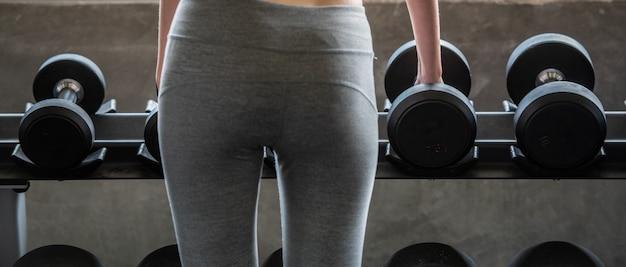 Тренировки женщина с поднятием тяжестей для стройного тела и тела стройная форма здания. Premium Фотографии