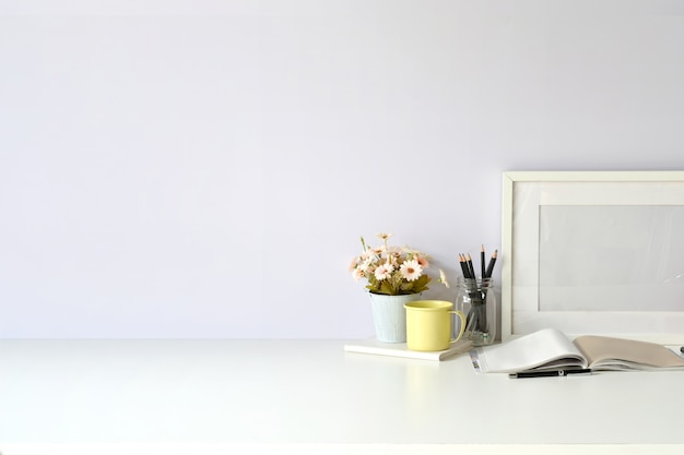 Workplace and copy space, stylish workspace with mockup blank poster, vintage books and house plant. Premium Photo