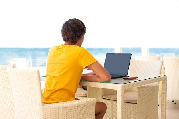바다가 보이는 카페에서 직장. 카페에서 노트북에서 일하는 남자. 공간을 복사하십시오. 모의. 프리미엄 사진