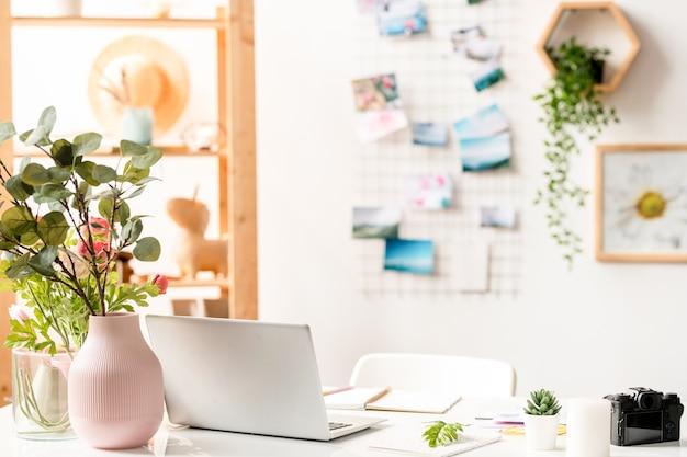 ラップトップ、事務用品、机の上に花の組成物を持つインテリアデザイナーの職場 Premium写真