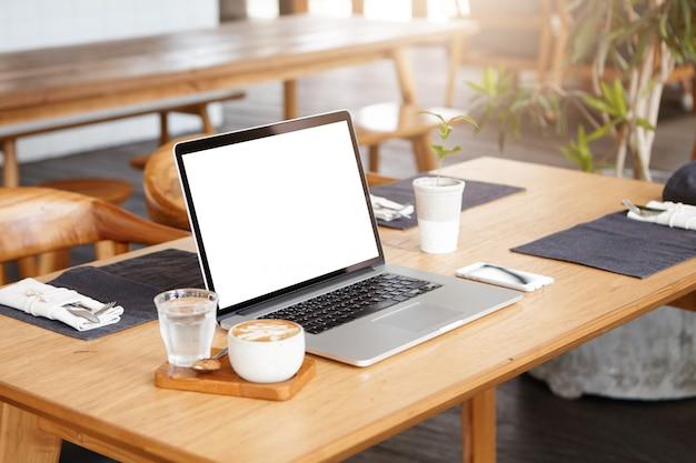 誰もいないときの未知のフリーランサーの職場:一杯のコーヒー、コップ一杯の水、携帯電話、一般的なラップトップpcのミニマリストショット 無料写真