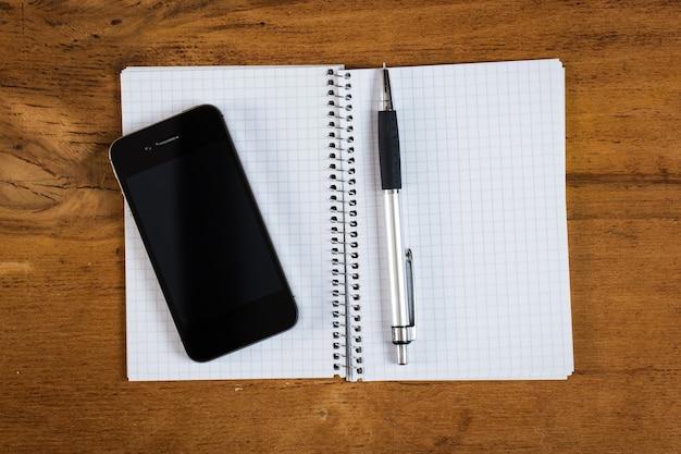 Рабочее место. телефон и блокнот на столе Бесплатные Фотографии
