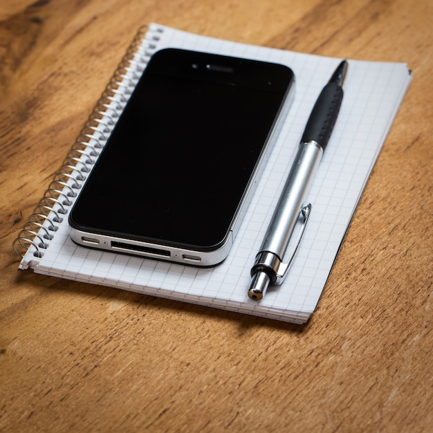 Posto di lavoro. telefono e blocco note sul tavolo Foto Gratuite