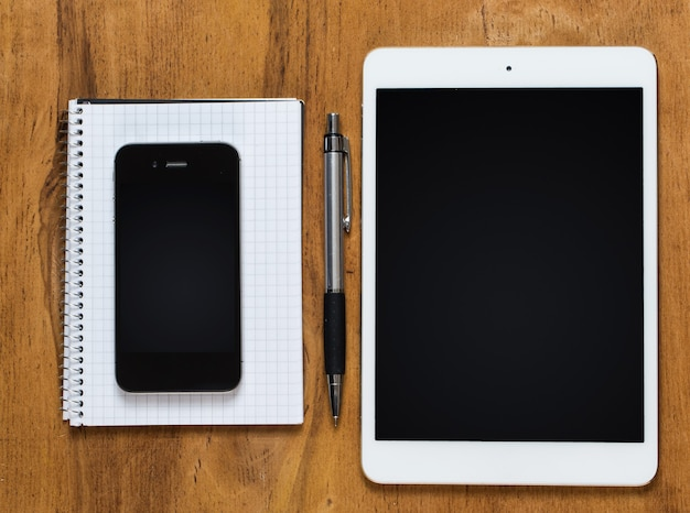 Posto di lavoro. telefono, tablet e blocco note sul tavolo Foto Gratuite