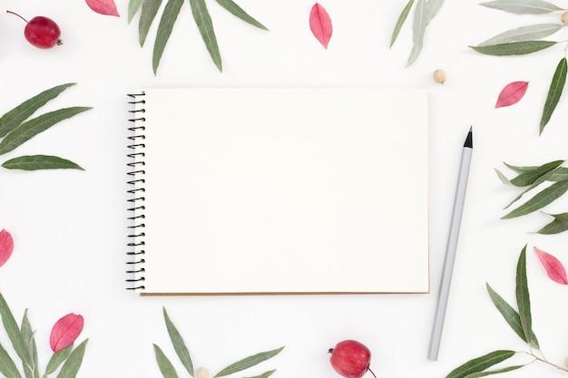 메모장 모형, 연필 및 흰색 테이블에 꽃 프레임 직장. 프리미엄 사진