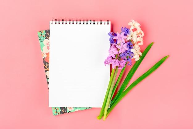 ピンクの背景にヒヤシンスの花の花束、白いメモ帳と職場フラット横たわっていたトップビューモックアップ Premium写真