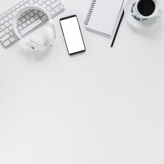 Workplace with electronic devices stationery and coffee cup on white table Free Photo