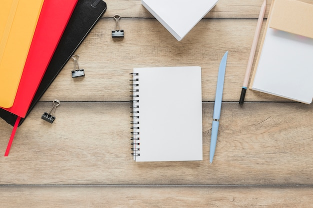 Workplace with notebook placed near stationery on wooden table Free Photo