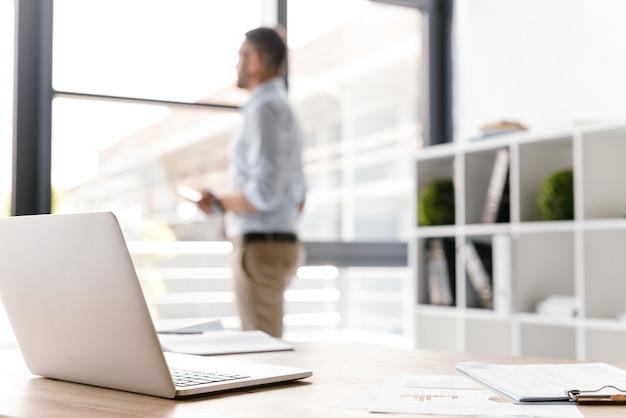 Defocused 비즈니스 남자가 서서 큰 창문을 통해보고있는 동안 테이블에 누워 열린 흰색 노트북과 직장 프리미엄 사진