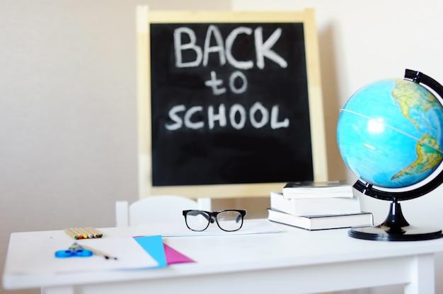 Workplace with school desk, blackboard, globe and eyeglasses. Premium Photo