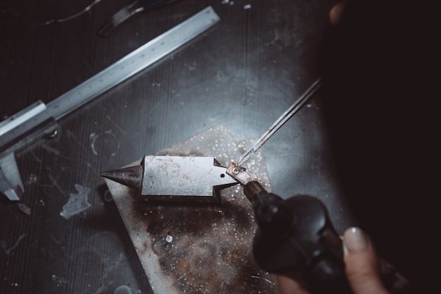 In the workshop, a woman jeweler is busy soldering jewelry Free Photo