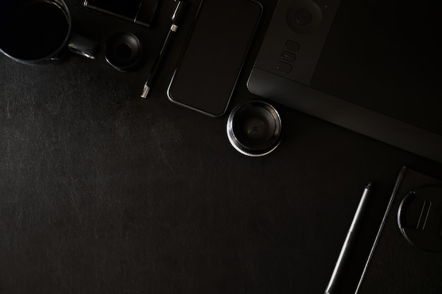 Workspace on black leather top table of a creative designer or photographer and copy space Premium Photo