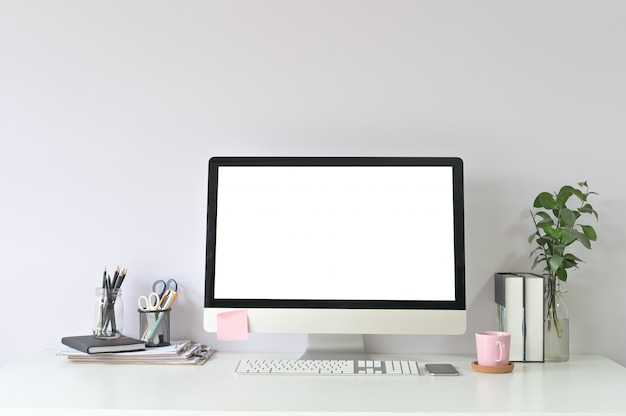 Workspace computer and office supplies on office workplace with mockup pc computer empty display. Premium Photo