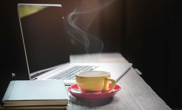Workspace concept in dark tone color with laptop and cup of coffee on wooden table. Premium Photo