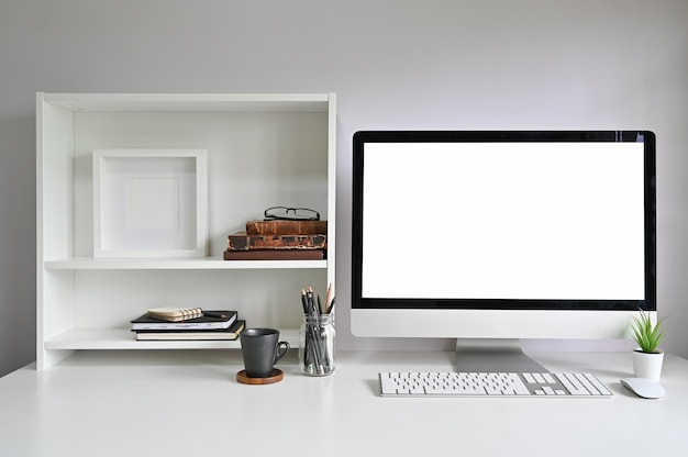 Workspace mockup computer on office desk and books, photo frame and books on shelves. Premium Photo