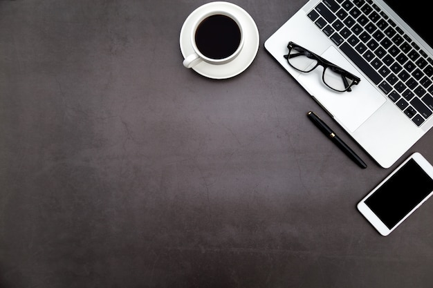 Workspace in office ,black desk with blank notebook and other office supplies. Premium Photo