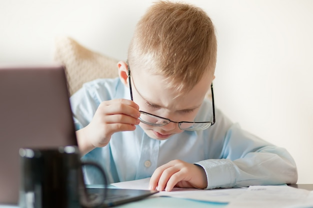 ノートパソコンと一杯のコーヒーとワークスペースのオフィスデスク。テーブルに座っていると重要なドキュメントを探しているかわいいビジネス少年。子供のオンライン学習。 Premium写真