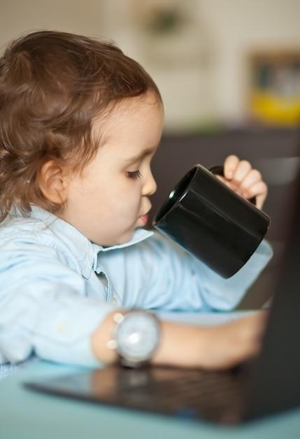 ノートパソコンとワークスペースのオフィスデスク。テーブルに座って、マグカップのコーヒーを飲んでかわいいビジネス少女。子供のオンライン学習。オンライン教育の遠隔学習。 Premium写真