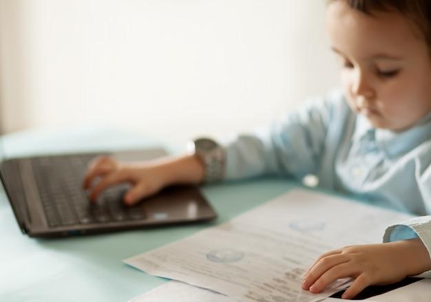 ノートパソコンとワークスペースのオフィスデスク。テーブルに座って、重要なドキュメントを探しているかわいいビジネスの少女。子供のオンライン学習。 Premium写真