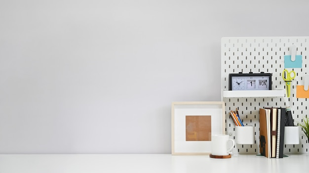 Workspace office supplies, coffee and photo frame on white creative table with copy space. Premium Photo