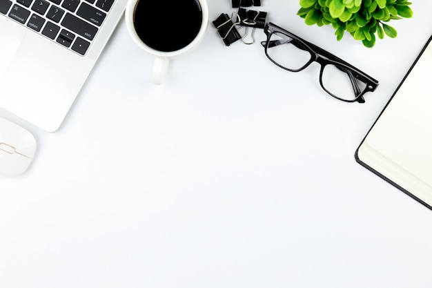 Workspace in office ,white desk with blank notebook and other office supplies Premium Photo