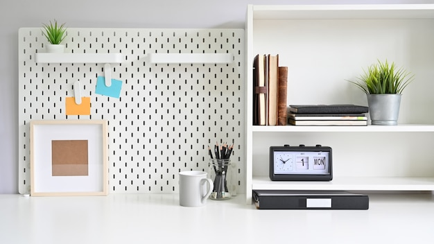 Workspace pegboard and shelves with office supplies Premium Photo