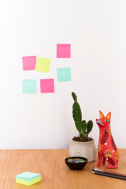 Workspace with cactus in pot and figurine on desk Free Photo
