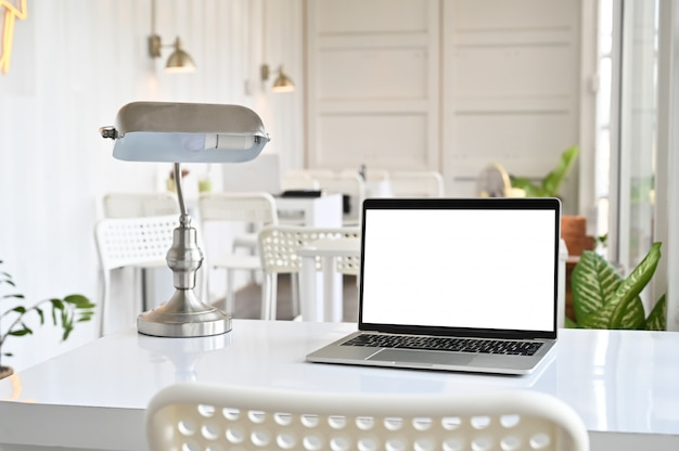 Workspace with computer laptop and lamp on office table with montage screen. Premium Photo