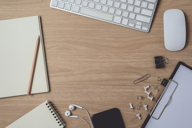 Workspace with diary or notebook and clipboard, mouse computer, keyboard, smart phone, earphone, pencil, pen on wooden Premium Photo