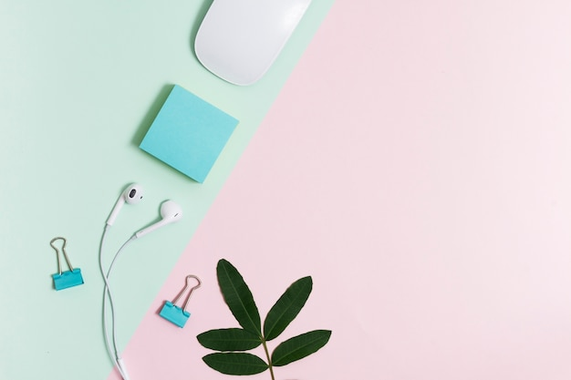 Workspace with earphones and mouse on pink and green background Free Photo