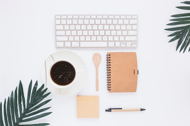 Workspace with keyboard cup and stationary Free Photo
