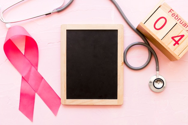 World cancer day awareness ribbon with stethoscope, wooden slate and 4th february wooden box Free Photo