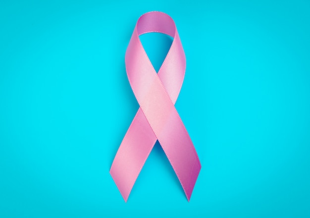 World cancer day : breast cancer awareness ribbon on blue backgr Free Photo