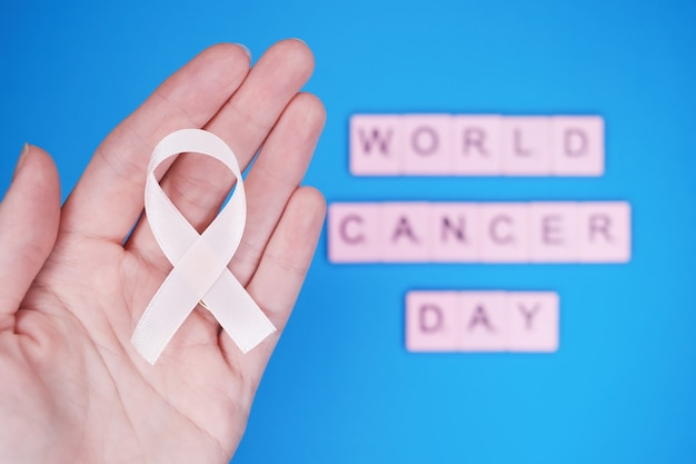 World cancer day, february 4th. woman holds pink ribbon on hand Premium Photo